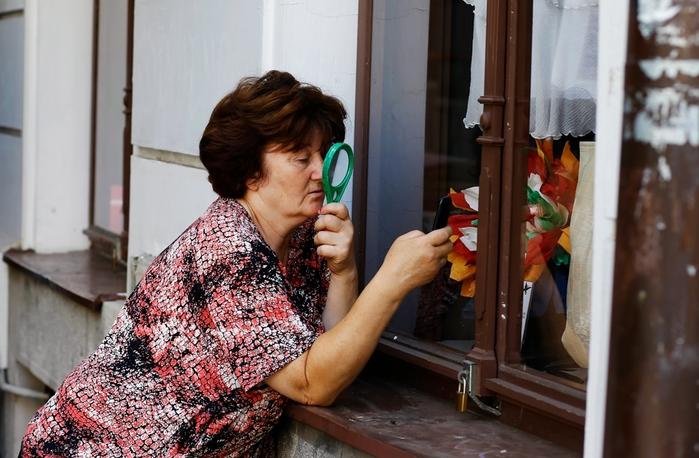 Женщина с увеличительным стеклом отправляет СМС
