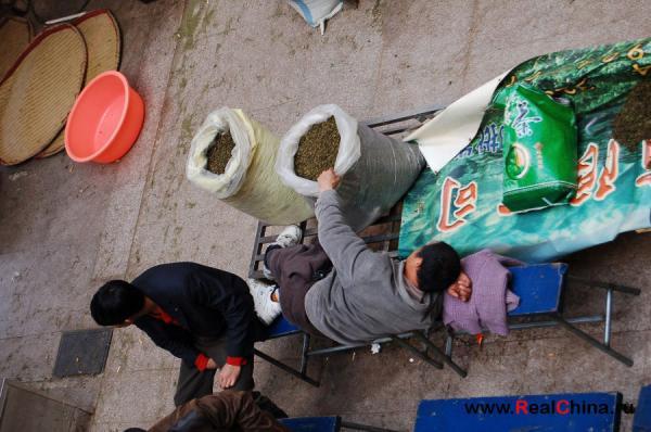 спящий китайский торговец держится за мешок