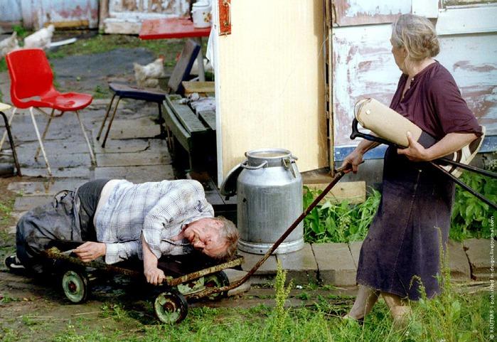 жена везет на тележке пьяного мужа фото агентства Рейтер взято из ЖЖ у пользователя drugoi, 1995