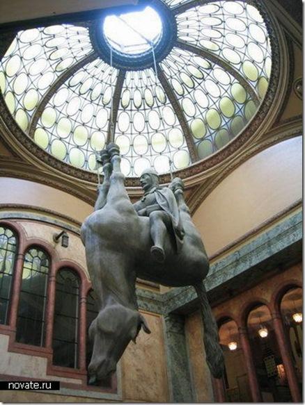 перевернутая подвешенная под куполом лошадь со скульптурой человека на ней