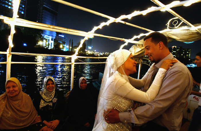 Egyptian groom Ayman Muhammad, 32, dances with his bride Mona as they take a midnight boat trip on the Nile River on June 1, 2009 in Cairo, Egypt. (David Silverman/Getty Images)