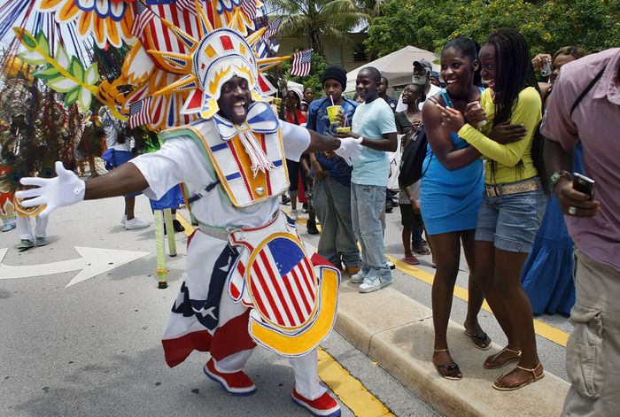 People enjoy the Junkanoo parade as a dancer passes by at the Goombay Festival on June 6, 2009 in Coconut Grove, Florida. The festival is a celebration of culture expression embracing the legacy of a Bahamian-rooted community. (Joe Raedle/Getty Images)