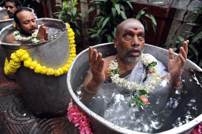 Индуистские святые садху читают мантры и молитвы во время ритуала Варуна Яджна, чтобы ублажить бога дождя в Санкара Маттхам в Мумбаи, Индия, 26 августа 2009 года. 10 жрецов стоят в воде по шею в течение 4 часов и читают специальные молитвы, чтобы вызвать дождь.