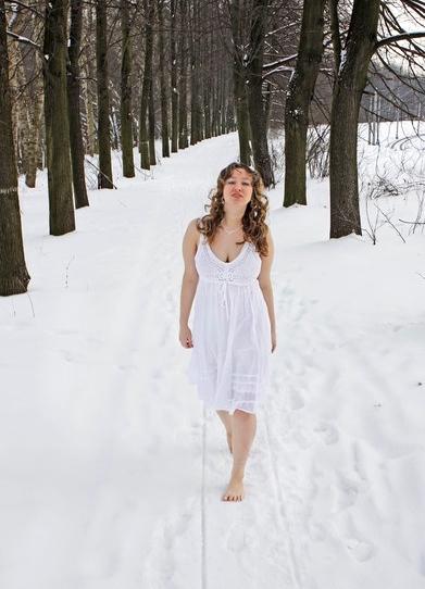 Девушка в белом платье идёт зимой босиком по аллее.