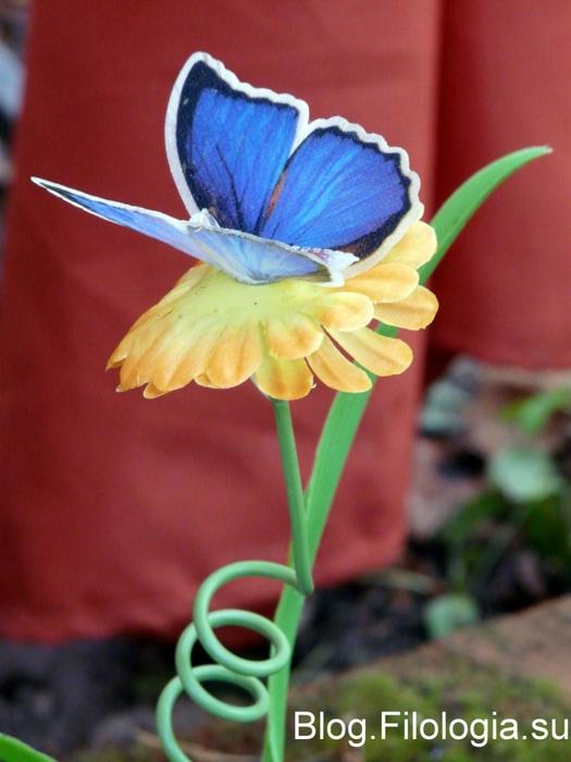 Игрушечная бабочка в саду