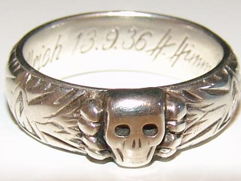 """Кольцо """"Мёртвая голова"""" представляло собой кусок серебра в виде венка из дубовых листьев, на котором располагались изображения мёртвой головы, двух зиг-рун, свастики, хайльсцайхена и хагалль-руны."""