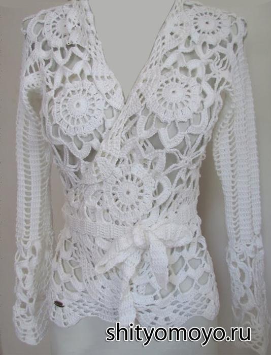 Края кофточки обвязаны ажурной оборкой.  Белая блузка с запахом и рукавами связана крючком из круглых мотивов.