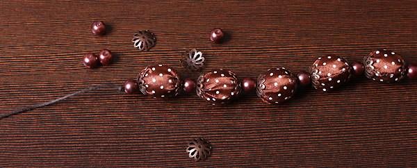 На вощеный шнур нанизываем поочередно то атласную, то жемчужную бусины (на атласные бусины с двух сторон одеваем...