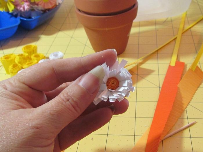 Теперь расправляем лепестки и получаем вот такой цветочек по форме напоминающий ромашку.