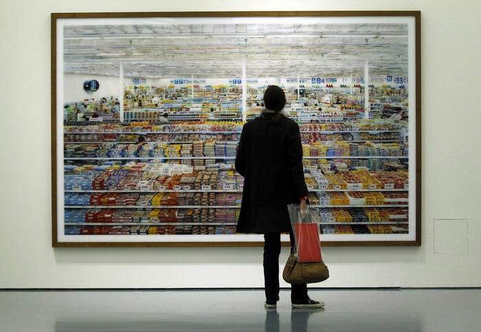 смотрит на фотографическую работу 99 центов Андреаса Гурски (Andreas Gursky) во время выставки в Музее Кунстпаласт (700x484, 123Kb)