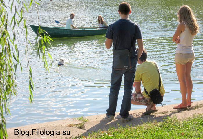 Компания молодых людей на берегу пруда в парке смотрит на катающихся на лодке (700x479, 85Kb)