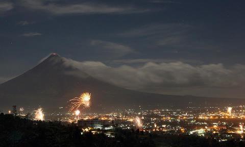 Новогодний салют освещает небо у вулкана Майон в Легазпи, провинция Албай, к югу от Манилы (480x288, 15Kb)