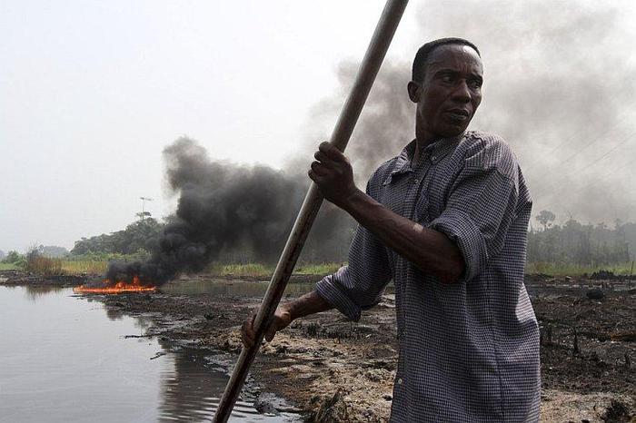 1. Нигериец плывёт в лодке недалеко от места, где взорвался нефтепровод. Причиной взрыва послужила попытка нелегальной врезки. 13 января 2013. Штат Байеса, Нигерия (700x466, 52Kb)