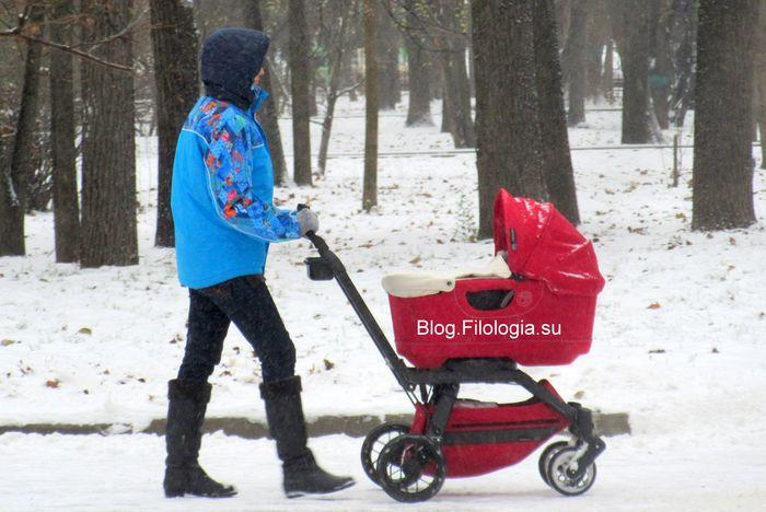 Девушка с красной детской коляской на фоне снега (700x468, 59Kb)