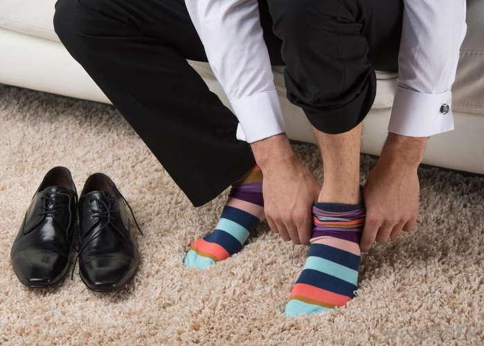man-putting-on-colorful-socks-on-carpet (700x500, 309Kb)