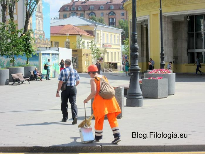 Женщина-дворник в яркой спецодежде подметает улицу летом в Москве