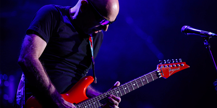 Joe-Satriani-Exploring-Three-Decades-Of-Shred-dark-w-red-guitar (700x350, 215Kb)