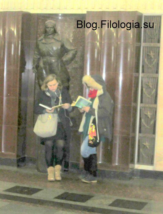 """Две девушки, читающие книги, на станции метро """"Площадь революции"""" в Москве"""