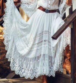 boho-style-maxi-dress-white-with-lace-hem-sleeves-and-inserts-worn-with-brown-leather-belt-with-iron-buckle-by-woman-standing-on-wooden-stairs (306x332, 110Kb)