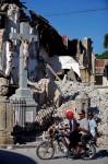 Жители проезжают мимо поврежденной церкви.