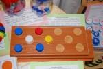 3 дощечки, на одной выложен рисунок из разноцветных крышек. На других работают дети - повторяют рисунок, либо придумай сам.