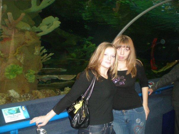 у большого аквариума с акулами.