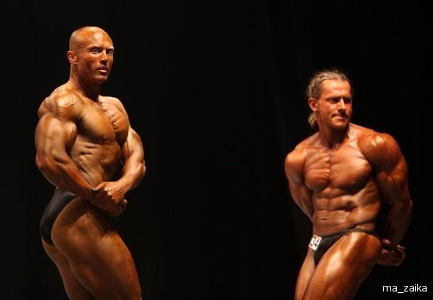 Культуристы позируют для судей в профессиональном туре конкурса Mister Universe