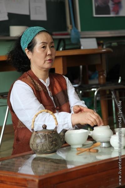 Салфетку кладут, а потом двумя руками закрывают чайничек крышкой.