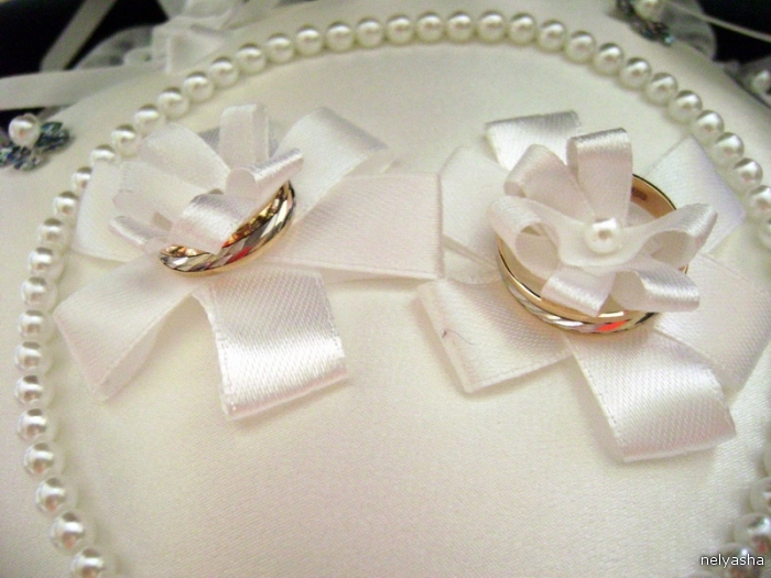 Engagement rings tucked in the first bows of narrow ribbon.