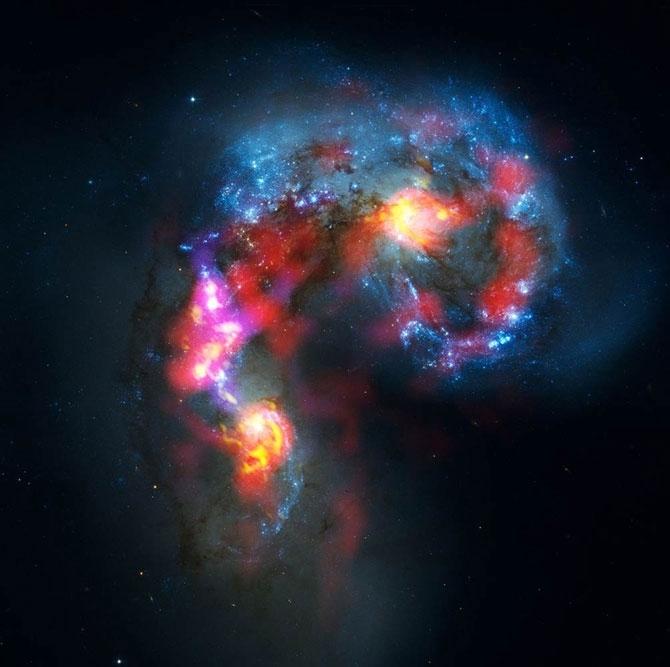 «Галактики антенны» – две галактики, находящиеся на расстоянии 70 миллионов световых лет в созвездии Ворона. Этот снимок был обнародован 3 октября. Он был получен с помощью двух телескопов – космического телескопа Хаббла и телескопа ALMA в Чили.