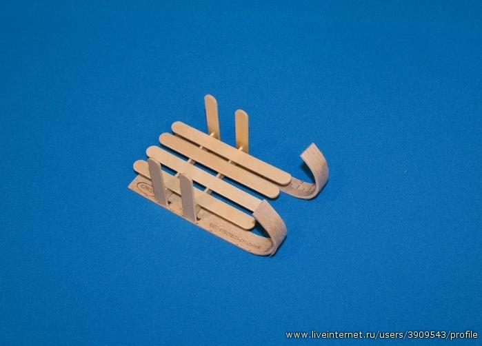 Наклейте на основание санок 4 палочки для мороженого. Они будут выполнять роль сиденья.