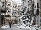 [+] Увеличить - Человек проходит мимо заснеженного здания в Хомсе, которое было повреждения во время боевых действий