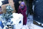 [+] Увеличить - Сирийский беженец перемещает стиральную машину чтобы защититься от снегопада в импровизированном лаг