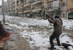[+] Увеличить - Сирийский боевик целится во время столкновений с проправительственными силами в Салахеддин окрестнос