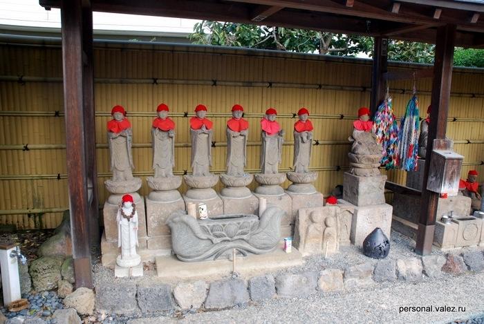 У входа в храмовый комплекс ряд статуй. На статуях вязанные шапочки и детские слюнявчики.