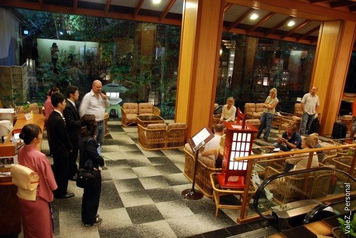 Встреча с менеджерами гостиницы у стойки ресепшн, за стеклом- красивый японский садик