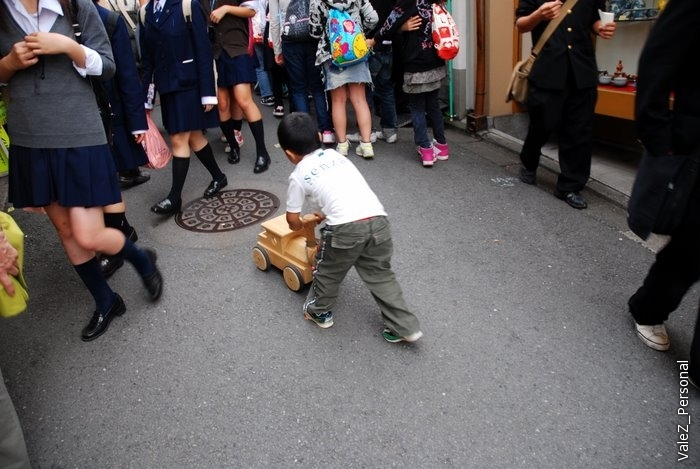 Посреди идущей толпы - мальчик играющий в деревянную игрушку, вот о ком про трудное детство, осталось только прибить её к полу:)