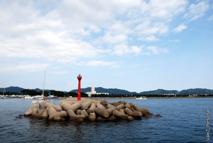 Маленький маяк сигнализирует о начале волнореза, обратите внимание на форму камней