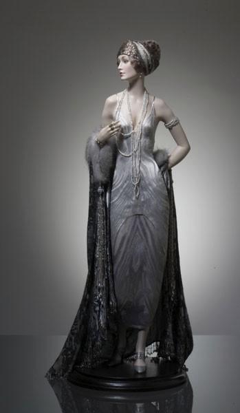 Нелли Платье 20-х годов 20 века  Шелковая ткань на платье окрашена вручную с переходом цвета. Шелковое пальто отделано натуральным мехом норки, кистями и бахромой, собранными из натурального речного жемчуга и антикварных декоративных элементов.  Головной