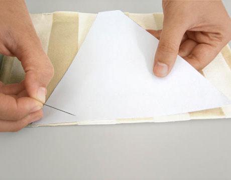 Coloque a capa do livro na borda de um pedaço de papel e abra-o em um ângulo de 45 °. Círculo no papel o triângulo resultante com uma borda chanfrada, adicione 1 cm de cada borda. Então, nós temos um padrão das partes laterais da bolsa