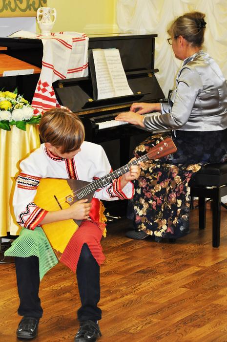 Арсений Малий играет на балалайке